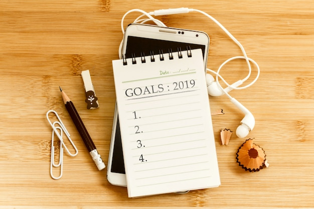 Notepad with  pencil and a smart phone on wooden table for new year goals 2019 concept