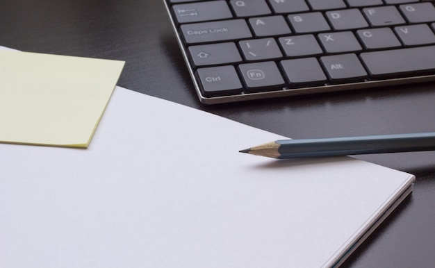 Notepad with a pencil on the table next to the keyboard, close-up