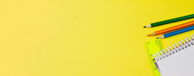 Notepad with pencils on a yellow background.