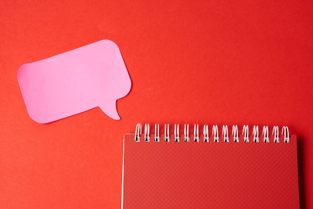 Notepad with pink sticky note on red background top view copy space. high quality photo