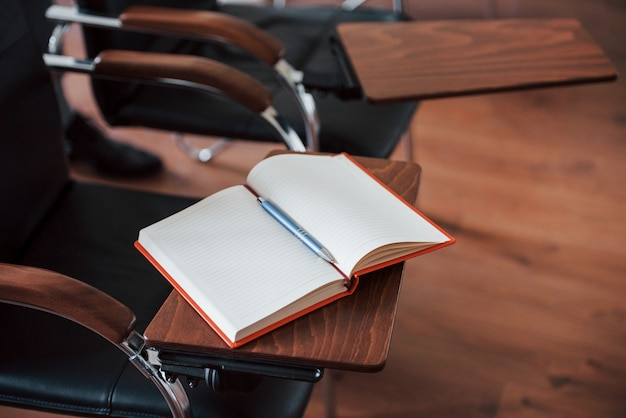 Notepad with red cover lying on the stand of chair in the business classroom