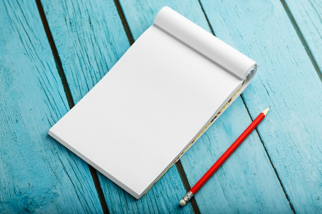Notepad with red pencil on a blue wooden table background, for education, write goals and deeds