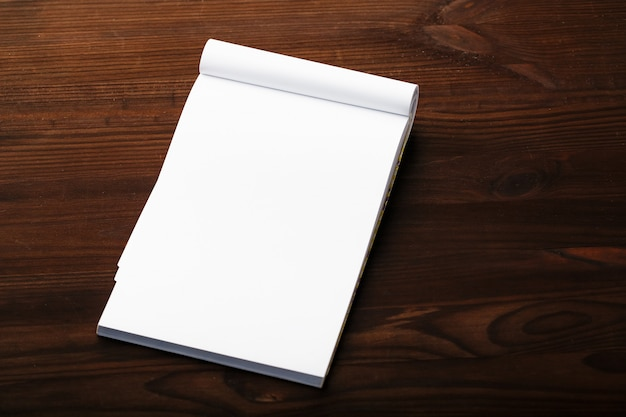 Notepad with red pencil on a brown wooden table background, for education, write goals and deeds
