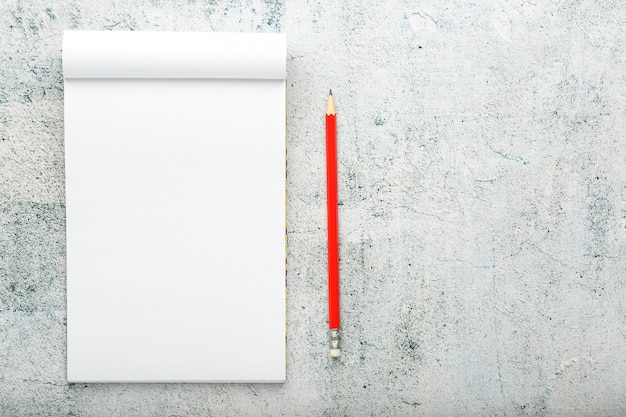 Notepad with red pencil on white plastered wall
