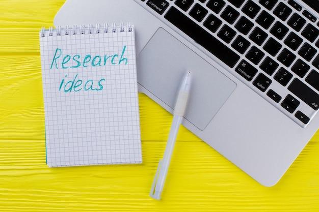 연구 아이디어와 펜이 있는 메모장. 노란 나무에 노트북 키보드입니다.