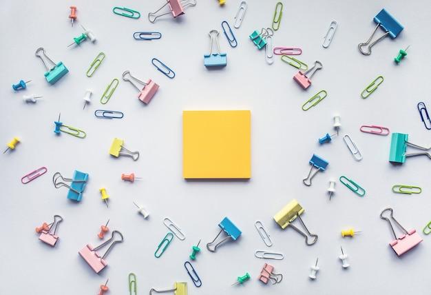 흰색 바탕에 다채로운 종이 클립 세트가 있는 메모장