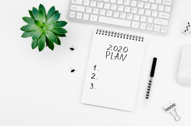 Notepad with stationery items and plant top view