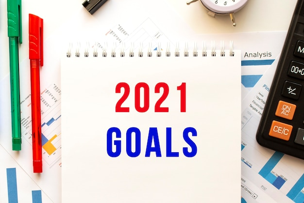 Notepad with the text 2021 goals on a color financial chart. pen, calculator on the office table.