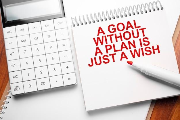Блокнот с текстом цель без плана - это просто желание на деревянном фоне с калькулятором и красным маркером