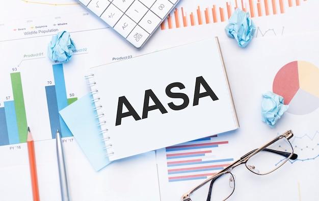 Блокнот с текстом aasa на бизнес-диаграммах и ручке, бизнес