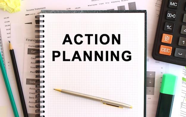 Блокнот с текстом планирование действий на белом фоне, рядом с калькулятором и канцелярскими принадлежностями.