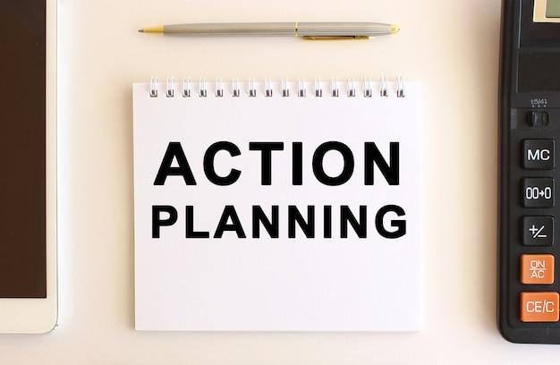 Блокнот с текстом планирование действий на белой поверхности. бизнес-концепция.