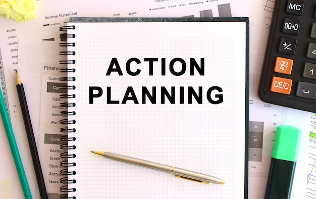 Notepad with text action planning on a white background, near calculator and office supplies.