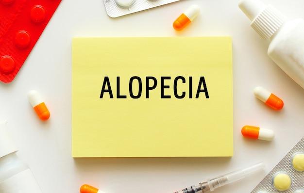 白い表面にテキストalopeciaが付いたメモ帳。近くには様々な薬があります