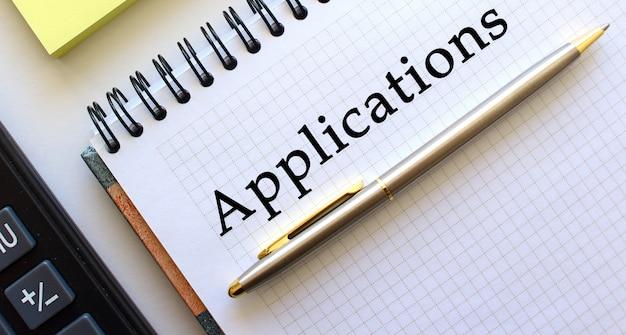 テキストapplicationsが書かれたメモ帳の横には、電卓と黄色のメモ用紙があります。ビジネスコンセプトです。