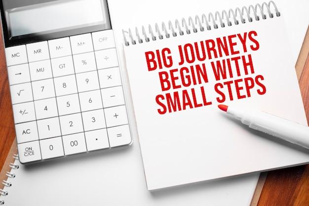 テキスト付きのメモ帳大きな旅は、電卓と赤いマーカーで木製の背景に小さなステップから始まります