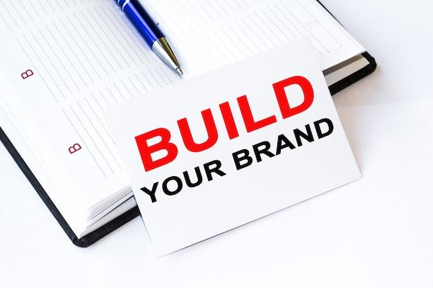 Блокнот с текстом создать свой бренд, скрепки, синюю ручку на финансовых диаграммах. бизнес-концепция