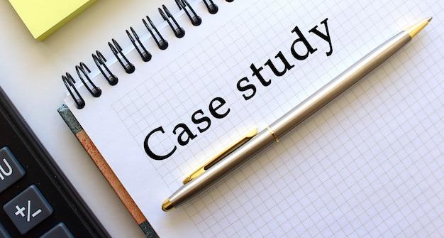 テキストケーススタディ付きのメモ帳、その横に電卓と黄色のメモ用紙があります。ビジネスコンセプトです。