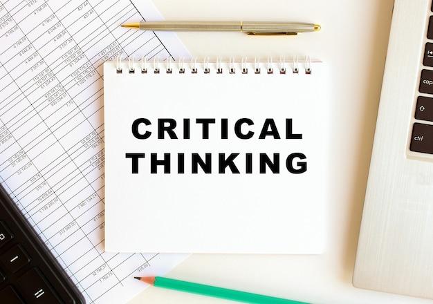 Блокнот с текстом критического мышления на белом фоне, возле ноутбука, калькулятора и канцелярских товаров.
