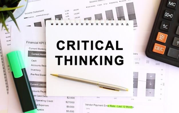 Notepad with text critical thinking on a white.