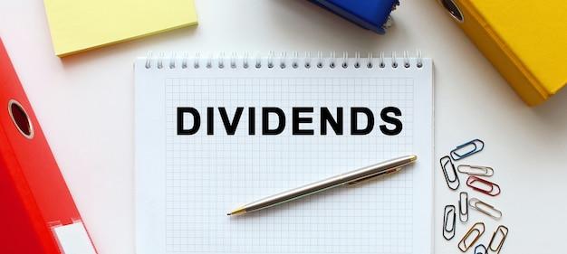 ドキュメントフォルダと事務用品の近くの白い背景にテキストdividendsのメモ帳