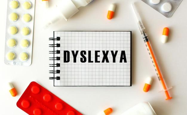 白い背景にテキストdyslexyaのメモ帳近くにはさまざまな薬があります