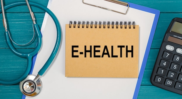 Notepad with text e-health, calculator and stethoscope