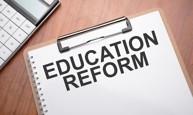 Блокнот с текстом реформы образования на деревянных фоне с зажимами, ручкой и калькулятором