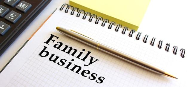 Блокнот с текстом семейный бизнес, рядом лежит калькулятор и желтые заметки.