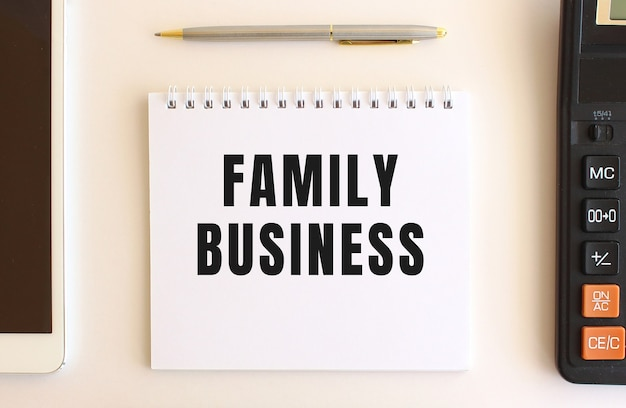 Notepad with text family business on a white background, near calculator, tablet and pen.