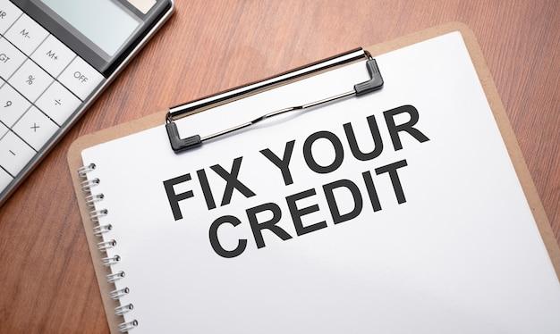 テキスト付きのメモ帳は、クリップ、ペン、電卓で木製の背景にあなたのクレジットを修正します