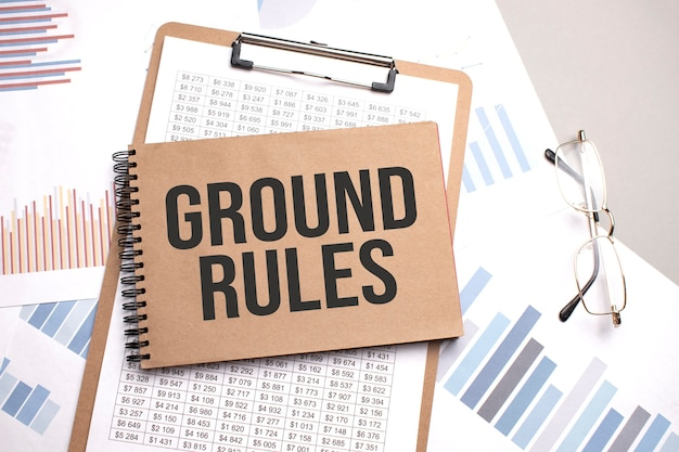 Notepad with text ground rules on a charts and numbers. business concept.