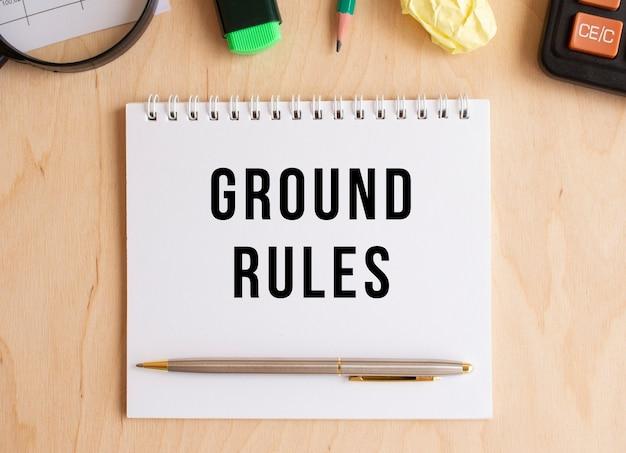 계산기 및 사무 용품 근처의 나무 테이블에 텍스트 접지 규칙이있는 메모장