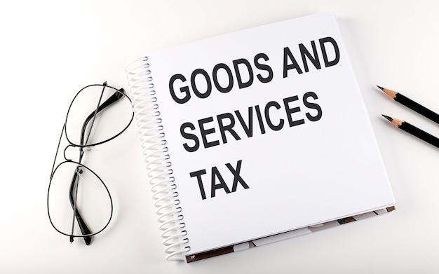 Gst가 상품 및 서비스 세금으로 표시된 메모장. 흰색 배경. 비즈니스 개념