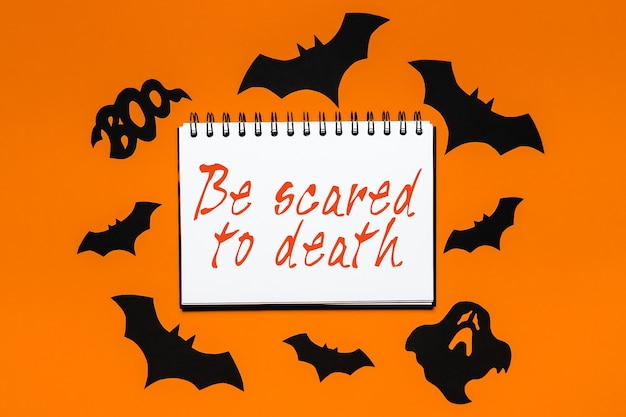 Notepad with text halloween be scared to death on white and orange background