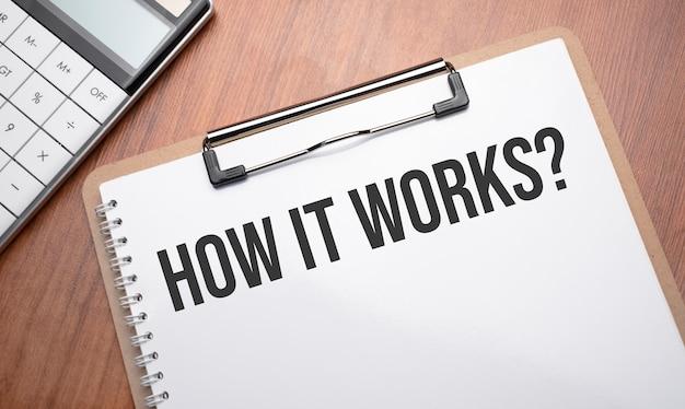テキスト付きのメモ帳クリップ、ペン、電卓を使用して木製の背景でどのように機能するか