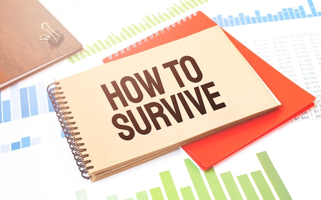 Notepad with text how to survive. diagram, red notepad and white background
