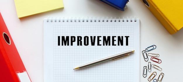 事務用品と白い背景の上のテキストの改善とメモ帳