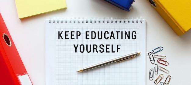 テキスト付きのメモ帳白い面、ドキュメントフォルダと事務用品の近くに自分自身を教育し続ける