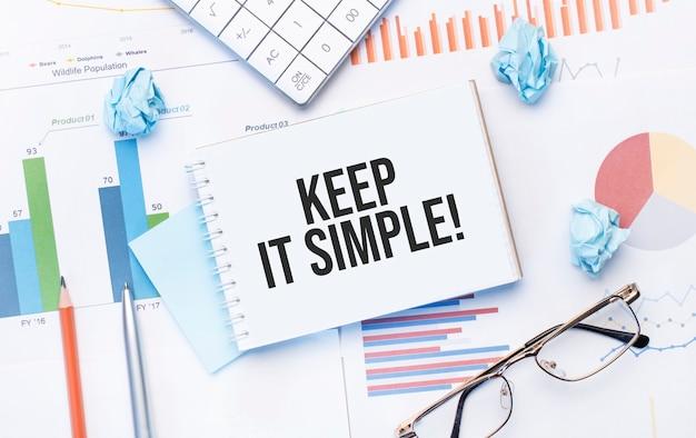 Блокнот с текстом keep it simple на бизнес-диаграммах и ручке, бизнес