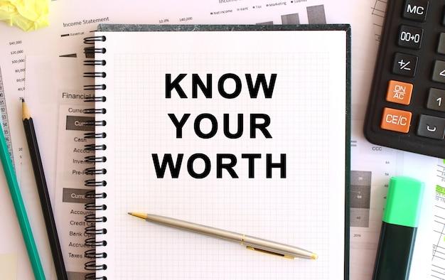 Блокнот с текстом знай свою стоимость на белом фоне.