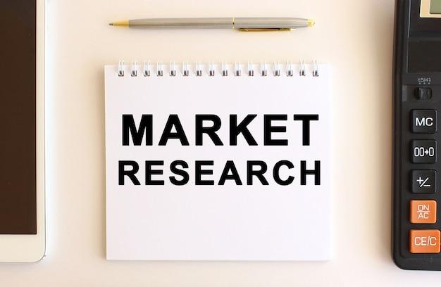 白地にテキストの市場調査が記載されたメモ帳