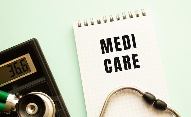 白い背景にテキストmedicare、電卓、聴診器が付いたメモ帳。医療の概念。