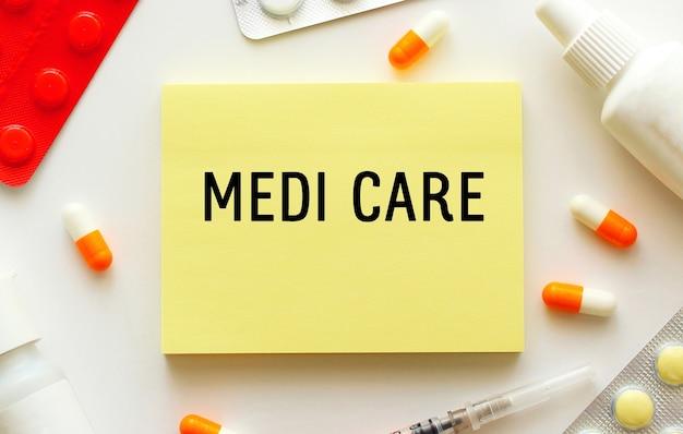 白い表面にテキストmedicareが付いたメモ帳。近くには様々な薬があります