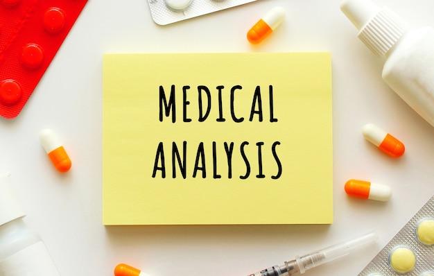 白い背景の上のテキスト医療分析とメモ帳。近くには様々な薬があります。