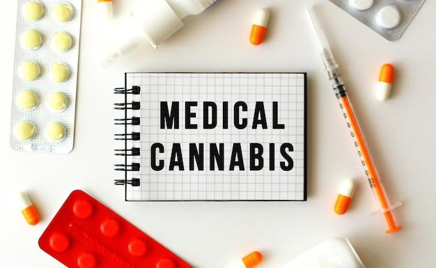 白い背景の上のテキスト医療大麻とメモ帳。近くには様々な薬があります。医療の概念。