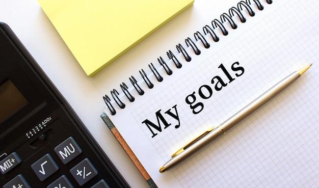テキストmy goalsが書かれたメモ帳の横には、電卓と黄色のメモ用紙があります。ビジネスコンセプトです。
