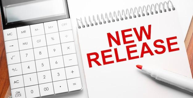 電卓と赤いマーカーで木製の背景にテキストの新しいリリースのメモ帳