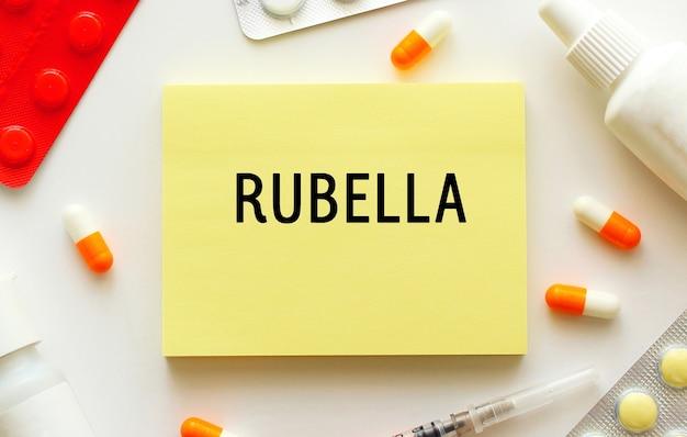 白い表面にテキストrubellaが付いたメモ帳。近くには様々な薬があります