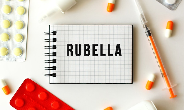 白い表面に風疹の文字が書かれたメモ帳。近くには様々な薬があります。